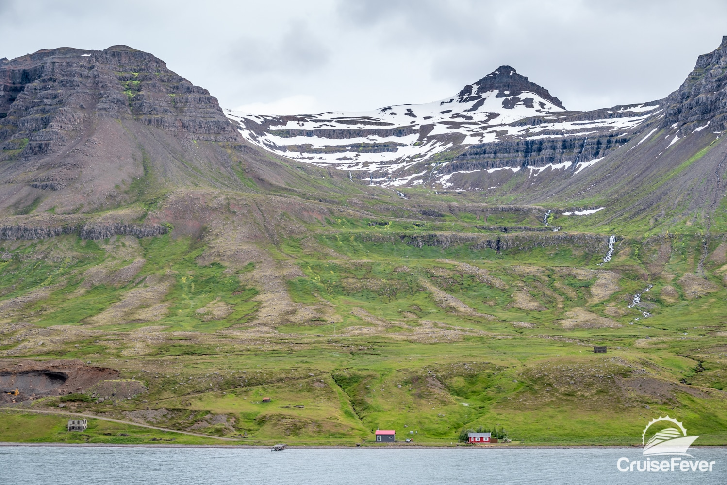 Red house at base of snow capped mountain near Seydisfjördur